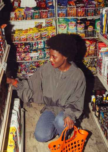 happy black woman choosing products in supermarket